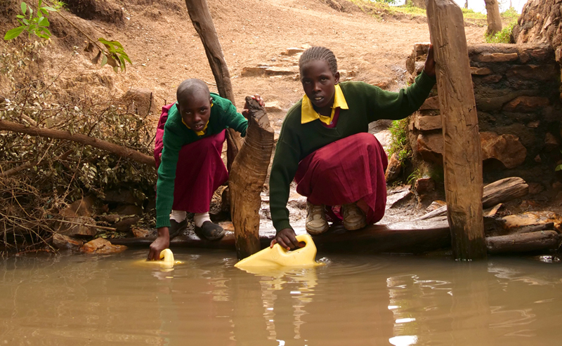 Girls fetching water from a dirty river.