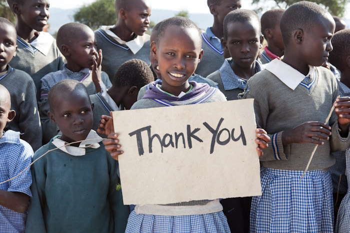 "Children in Kenya holding a sign that says, ""Thank You."""